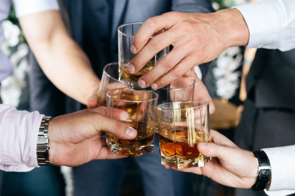 People toasting glasses of whiskey