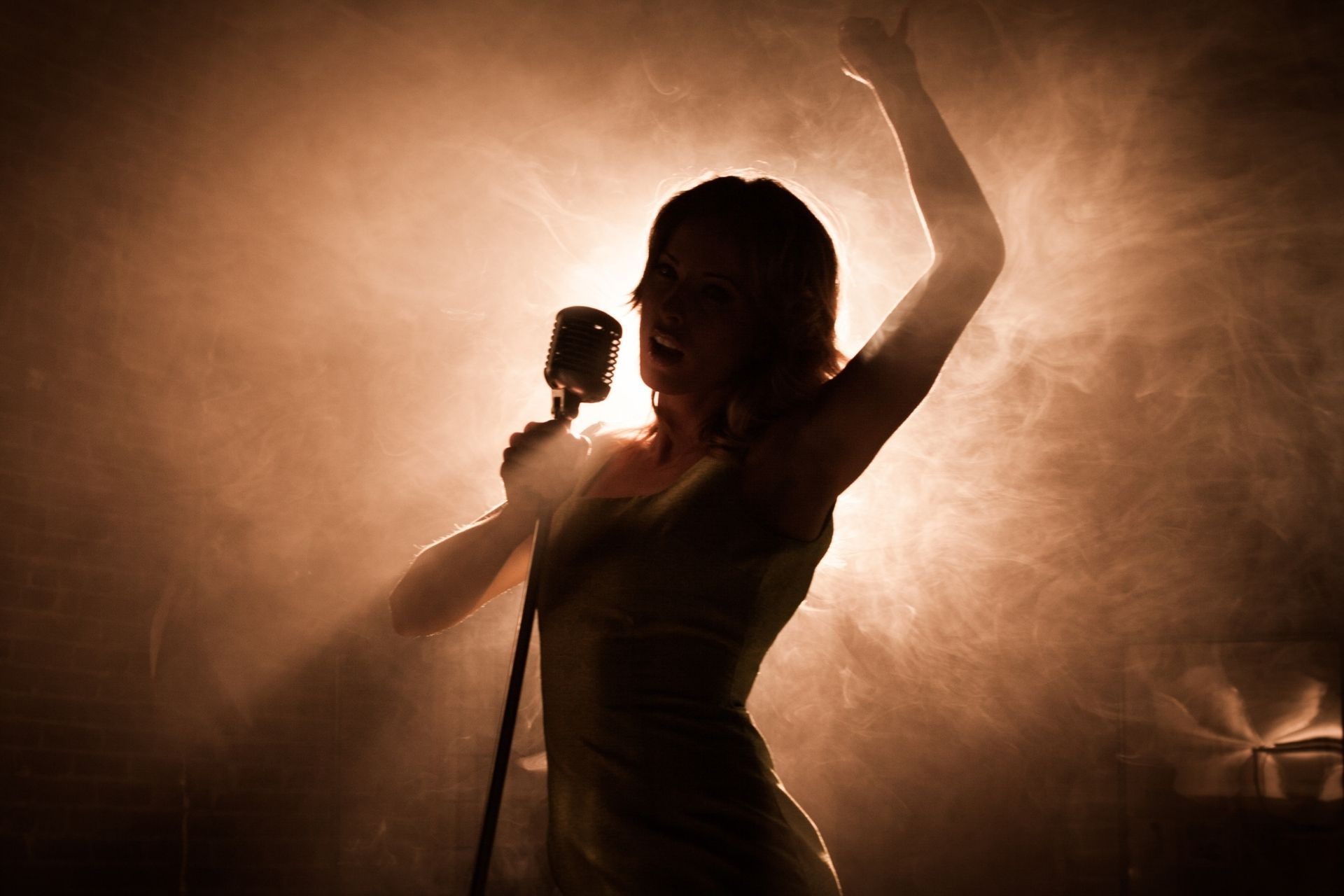 A silhouette of a woman singing into a microphone