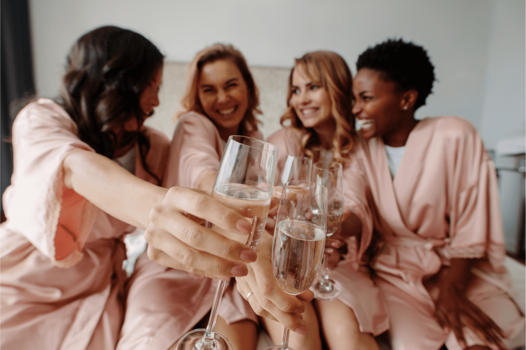 Four women clinking their champagne flutes in bathrobes